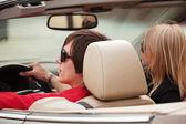 Pareja joven en un coche descapotable — Foto de Stock