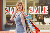 Young woman against a shop window — Stock Photo