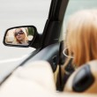 Young woman looking in the car mirror — Stock Photo