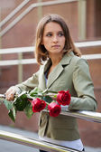 Sad young woman with a red roses — Stock Photo