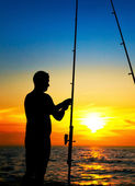Fishermen boy fishing at beautiful sunset — Stock Photo