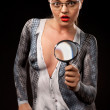Shocked woman with magnyfing glass and bodypainting — Stock Photo