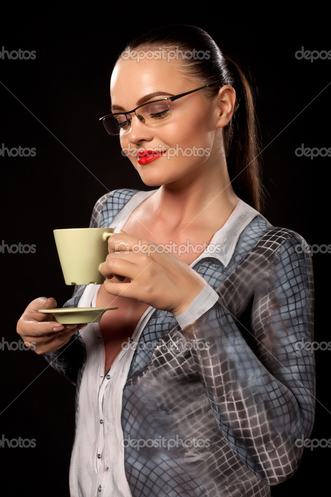 Happy sensual woman holding a green coffe or tea cup. She is naked, covered in business suit bodypainting. High resolution studio image on black background. Concept for sexual issues at work.  Stock Photo #11008965