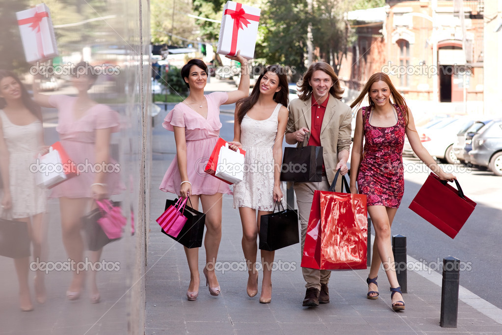 Group of four happy fashionable friends walking on the street smiling and holding colorful shopping bags. — Stock Photo #11289260