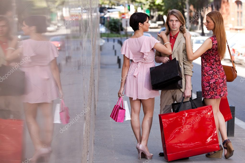 Group of an handsome young man with two beautiful women with colorful shopping bags on the street. Concept for temptation — Stock Photo #11289261