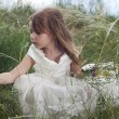 Fairy-tale beautiful little girl on a lawn with the field flower — Foto de Stock