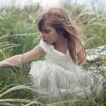 niña hermosa cuento de hadas en el césped con la flor de campo — Foto de Stock