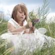Fairy-tale beautiful little girl on a lawn with the field flower — Stockfoto