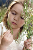 Portrait of beautiful little girl with the field flowers — Stock Photo