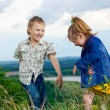 A little girl and boy play and cheered on a walk outdoors — Stock fotografie