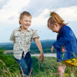 Foto de Stock  : A little girl and boy play and cheered on a walk outdoors