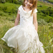 Beautiful girl in the clothes of bride on the field with the fie — Stok fotoğraf