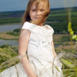 Foto Stock: Beautiful girl in the clothes of bride on the field with the fie