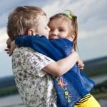pequeño niño y niña se besó sobre un fondo de un paisaje — Foto de Stock