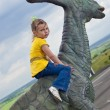 Little brave girl on a dinosaur in a park — Stock Photo