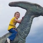 chica valiente de un dinosaurio en un parque — Foto de Stock