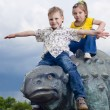 Little brave children on a dinosaur in a park — Stock Photo