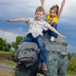 Little brave children on a dinosaur in a park — Stock fotografie