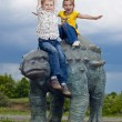 Little brave children on a dinosaur in a park — Stock Photo #11040971