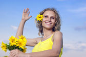 Beautiful young girl with sunflowers on a background clouds — Stock Photo