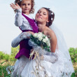 Wonderful young bride and beautiful little girl outdoors — Stock Photo #11124160