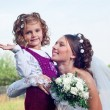 Wonderful young bride and beautiful little girl outdoors — ストック写真
