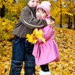 Stock Photo: Little boy and girl play in park in autumn