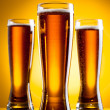 Three glass of beer over yellow background — Stock Photo