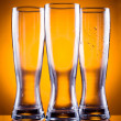 Three empty glass glasses for beer or drinks on a yellow backgro — Stock Photo