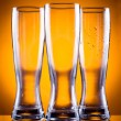 Three empty glass glasses for beer or drinks on a yellow backgro — Stock Photo #11125499