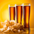 Stock Photo: Three glass of beer and potato chips on yellow background