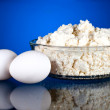 Fresh eggs and curd on a dark blue background — Stock Photo