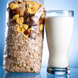 Fresh Glass of Milk and Closed Pack of muesli on a blue backgrou — Foto Stock