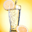 Pouring of mineral water in glass with a lemon on a yellow backg — Stock Photo