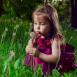 Beautiful little girl on a lawn with dandelions — Stock Photo #11144547