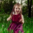 Beautiful little girl on a lawn with dandelions — Stock Photo