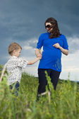Little boy is a daryl a pregnant mother the field flowers — Stock Photo