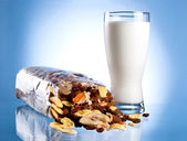 Fresh Glass of Milk and Opened Pack of muesli on a blue backgrou — Stock Photo