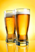 Two glasses of beer close-up with froth over yellow background — Stock Photo