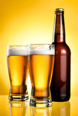 Two glasses and Bottle of fresh light beer on yellow background — Stock Photo
