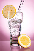 Pouring of mineral water in glass with a lemon on a pink backgro — Stock Photo