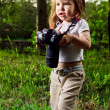 Amusing little girl takes pictures a professional camera — Stock Photo