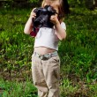 Royalty-Free Stock Photo: Amusing little girl takes pictures a professional camera