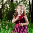 Beautiful little girl on lawn with dandelions — Stock Photo #11302296