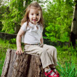 Amusing little girl sits on a hemp — Stockfoto