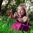 Beautiful little girl on a lawn with dandelions — Stock Photo #11302379