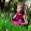 Stock Photo: Beautiful little girl on lawn with dandelions