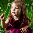 Beautiful little girl on a lawn with dandelions — Stock Photo #11302650