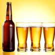 Three glasses and Bottle of fresh light beer on yellow backgroun — Stock Photo