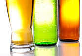 Bottom of the brown and green bottles with a full glass of beer — Stock Photo